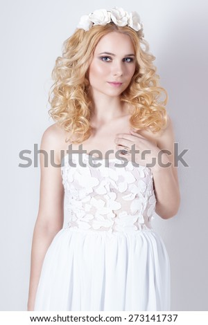beautiful lovely gentle elegant young blond woman in a white sundress chiffon and curls, and a wreath of flowers in her hair