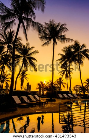 Beautiful luxury outdoor umbrella and chair around swimming pool with silhouette coconut palm tree in hotel resort - Vintage Filter