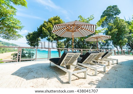 Beautiful luxury umbrella and chair decoration in hotel resort neary tropical beach and sea on blue sky background