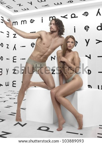 beautiful man and woman Adam and Eve, posing in the room with the alphabet on the walls of the white cubes