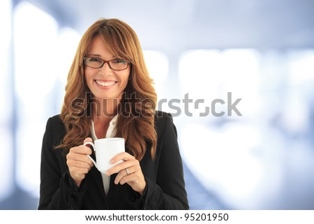 Beautiful mature woman drinking a cup of coffee in her office. (with copy space.)