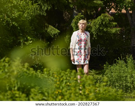 Beautiful mature woman in a garden, sunny summer day