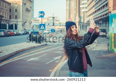 Beautiful Middle Eastern girl with long hair taking a selfie in the city streets