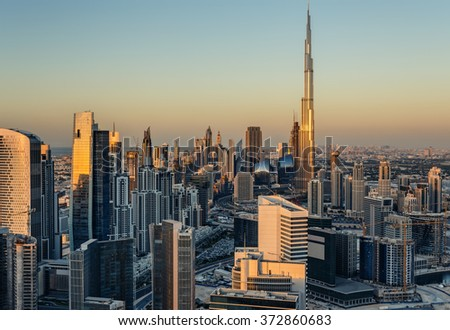 Beautiful modern city architecture at golden sunset. View of Dubai's business bay towers.