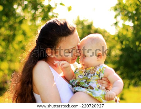Beautiful Mother And Baby outdoors. Nature. Beauty Mum and her Child playing in Park together