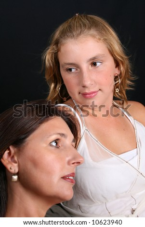 Beautiful mother and daughter on a black background