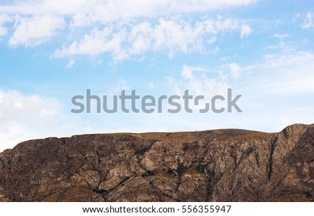 Beautiful mountain landscape in Uzbekistan. Mountains against the blue sky. Red rocks before the cliff. Majestic mountains Chimgan. On the slopes of the mountains grow small trees and some grass.