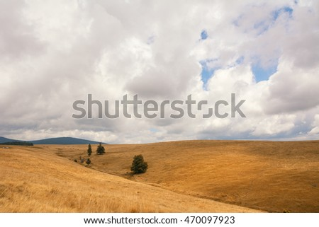 Beautiful mountain landscape with dry grass and a cloudy summer day