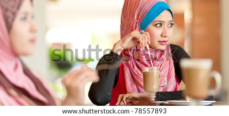 Beautiful Muslim women having lunch at coffee shop