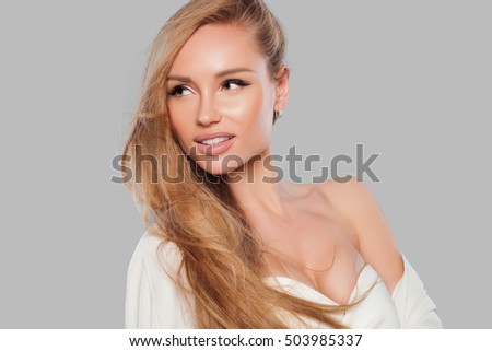 Beautiful natural woman with fashion make-up and blonde hair, portrait of an young girl isolated on gray