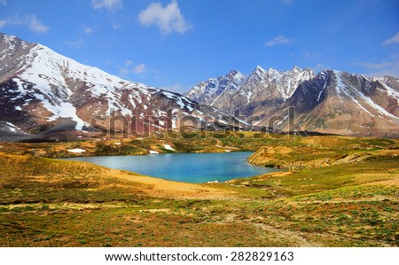 Beautiful nature scenery with bright blue lake in desert valley, mountain range covered with snow against the background of blue sky in Himalaya, Ladakh, Jammu & Kashmir, Northern India, Central Asia