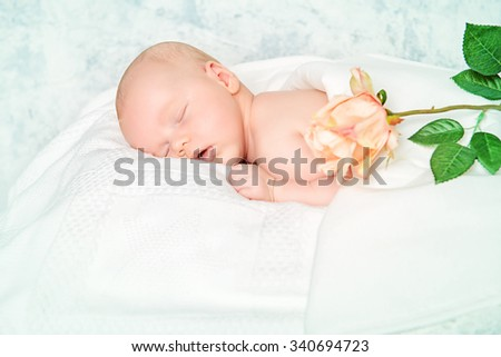 Beautiful newborn baby sleeps peacefully on a soft white blanket among the flowers.