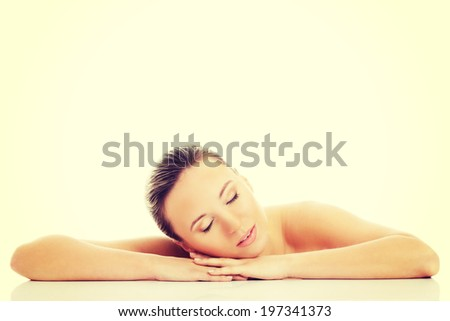 Beautiful nude woman is lying on her hands