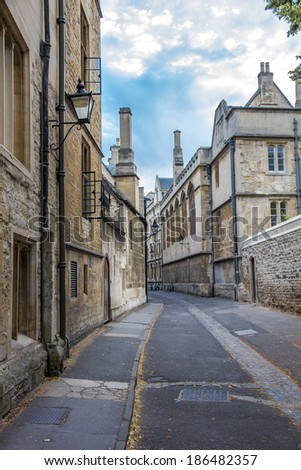 Beautiful old street In Oxford, England with old houses, decorative lanterns and blue sky in background, vertical