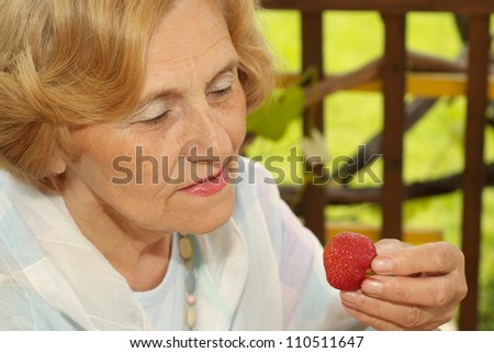 Beautiful old woman with strawberries on the nature