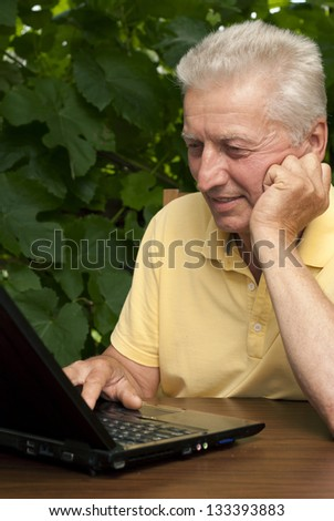 Beautiful older man sitting at a table at home on the veranda