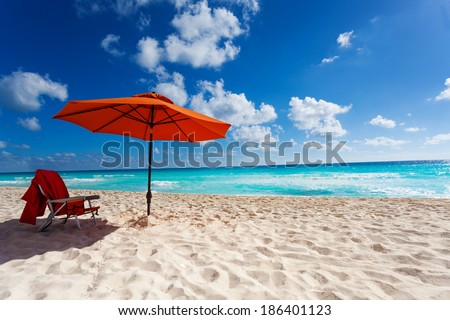 Beautiful orange umbrella and chair on the white sand beach