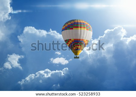 Beautiful peaceful background - hot air balloon rises very high in blue sky above white clouds, bright sun shines
