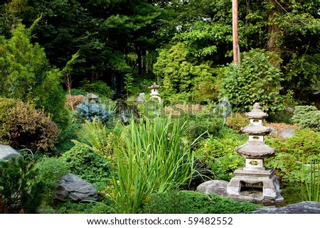 Beautiful peaceful Japanese zen garden used for meditation and relaxation, filled with green vegetation and granite Rokkaku Yukimi Lanterns.