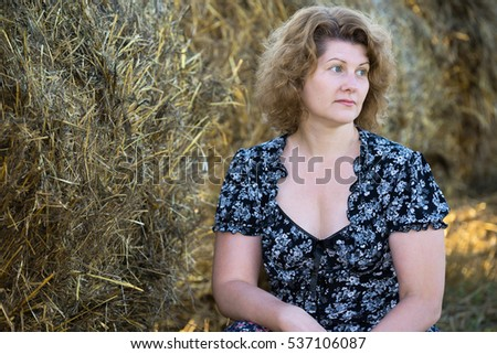 Beautiful pensive woman in a field on a background of straw bales