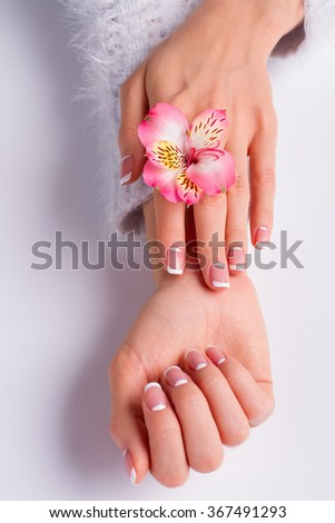 Beautiful pink freesia with franch moon manicure on a white background.