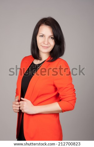 Beautiful portrait of a smiling business woman, over gray background.
