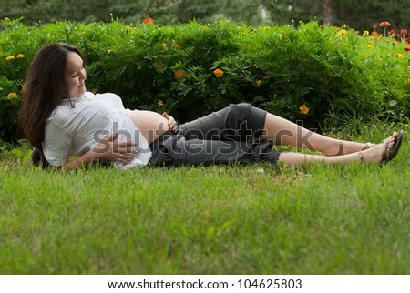 Beautiful pregnant asian woman relaxing on grass