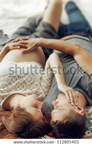 Beautiful pregnant wife holding hands on belly with helpful husband, future parents lying in bed. gentle moments of motherhood concept