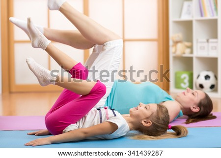 Beautiful pregnant woman and child daughter at gym fitness exercise practicing aerobics on mat