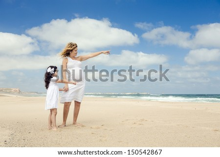 Beautiful pregnant woman and her little daughter on the beach pointing to the sea