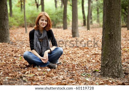 Beautiful red-haired girl in autumn park. Outdoor photo.