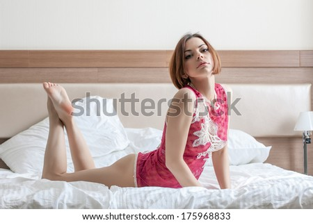 Beautiful red-haired girl lying on bed in hotel