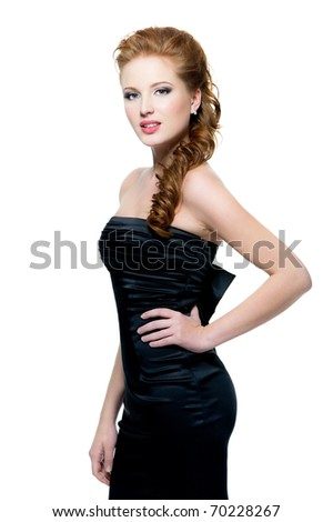 Beautiful  red-haired sensual woman in black dress posing on white background