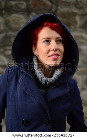 Beautiful redhead girl in blue coat with large hood looking up