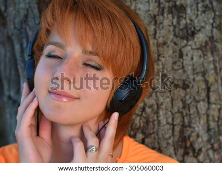 Beautiful redhead girl with freckles in a park listening to the sound of music in the headphones