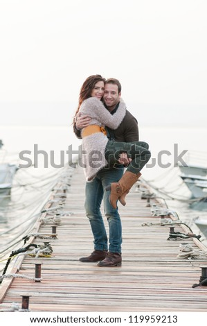 Beautiful relaxed couple on wooden pier in marina