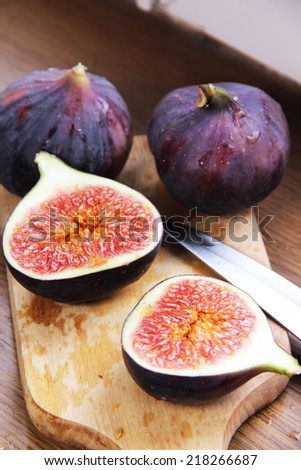 Beautiful ripe fresh pulpy figs on the wooden table