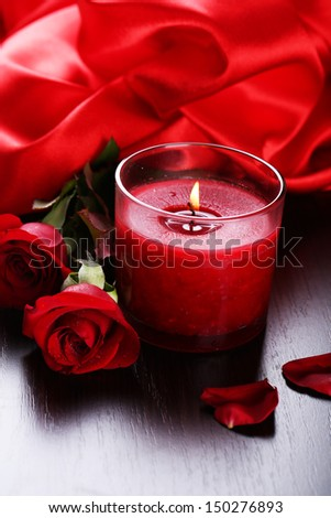 Beautiful romantic red candle with flowers and silk cloth, close up