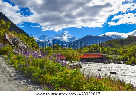 Beautiful rural landscape with high snowy mountains and river with bridge along with green forests and spring flowers