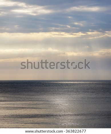 Beautiful seascape with dramatic sky and the sea. Sunlight breaks through the clouds.
