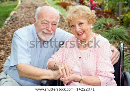 Beautiful senior couple outdoors.  The wife is in a wheelchair.