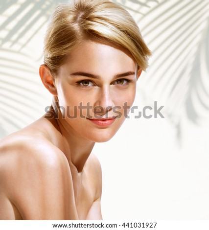 Beautiful sensual blonde woman of  European appearance on background with palm leaf shadows. Youth and skin care concept