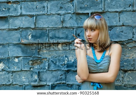 Beautiful sexual girl blonde beside sulphur concrete wall