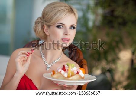 Beautiful sexy blonde woman in restaurant cafe with ice cream tiramisu