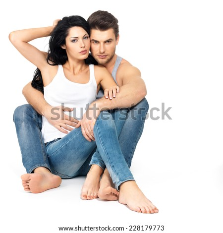 Beautiful sexy couple in love on white background dressed in blue jeans and white undershirt