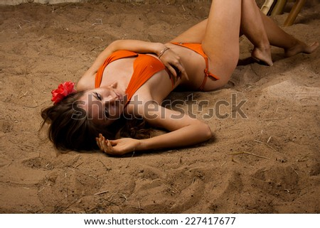 Beautiful sexy girl with a red flower in long hair in an orange bikini on the sunny beach. She is isolated on a bamboo background