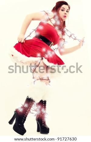 Beautiful sexy young woman tangled up in Christmas lights. Retro style photography.