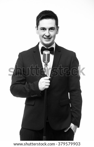 Beautiful showman in suit singing at the microphone and look at camera. Isolated on white background. Showman concept. Monochrome photography
