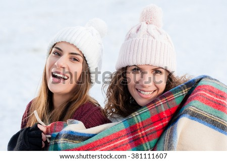Beautiful sisters wrapped in blanket in snow, looking and smiling at camera.