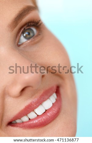 Beautiful Smile. Closeup Of Beautiful Happy Smiling Woman With White Teeth And Fresh Face. Beauty Girl With Cosmetic Lip Balm On Her Full Lips. Dental Health, Lip Care Concept. High Resolution Image